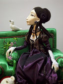 A collectible doll on green sofa with pigeon — Stock Photo