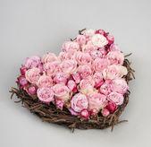 Roses in heart shape in a wooden weaving — Stock Photo