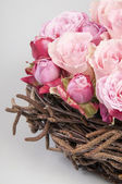 Roses in a wooden weaving — Stock Photo