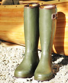Green boots on the rocks — Stockfoto