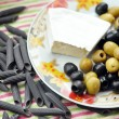 Brie cheese and olives on a plate — Stock Photo