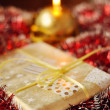 Stockfoto: Christmas present and lit candle on red background