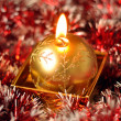 Golden Christmas candle on the red background — Stock Photo