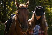 Cowgirl in hat with bay horse — Stock Photo