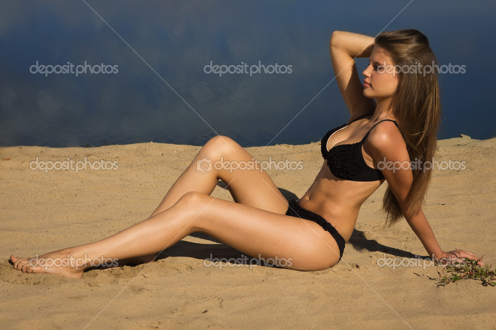 Attractive girl in a bikini on a sandy beach — Stock Photo #12670604