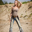 Cowgirl in jeans on a sandy background - Stock Photo