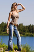 Cowgirl in jeans stands on the bank of forest river — Stock Photo