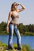 Cowgirl in jeans steht am ufer des waldes — Stockfoto