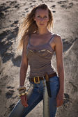 Cowgirl in jeans on a sandy background — Photo