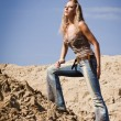 Cowgirl in jeans on a sandy background — Stock Photo