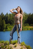 Cowgirl in jeans stands on the bank of forest river — Foto de Stock
