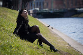 Beautiful young woman sitting at the river channel — Stock Photo