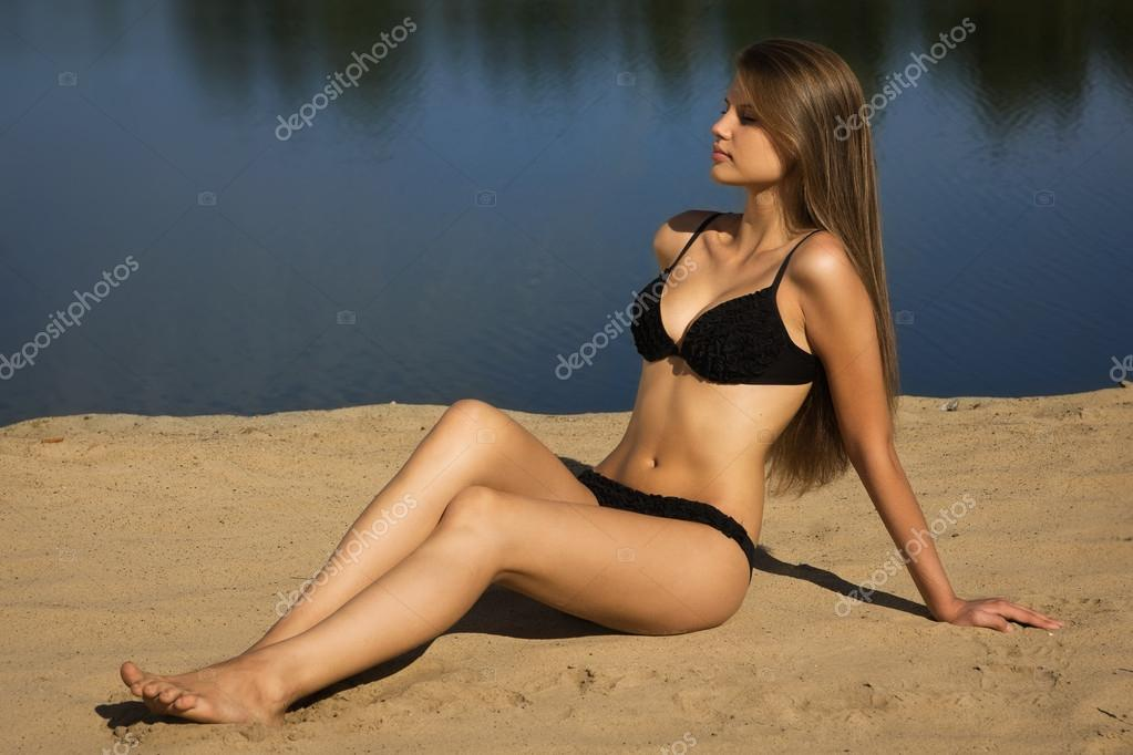 Attractive girl in a bikini on a sandy beach — Stock Photo #12899661