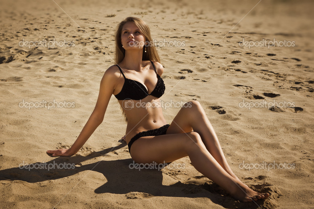 Attractive girl in a bikini on a sandy beach — Stock Photo #12899793