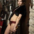 Sexy woman with a sword in a medieval castle interior - Stock fotografie