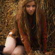 Pretty girl resting on straw bale — Foto Stock