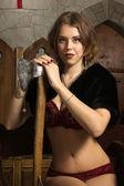 Sexy vrouw met bijl in een middeleeuws kasteel — Stockfoto