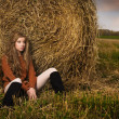 Stock Photo: Beautiful woman near a haystack