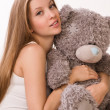 Sensuality girl with teddy-bear sitting on a sofa - Stock Photo