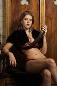 Mujer sexy con un cuerno en el interior de un castillo medieval — Foto de Stock