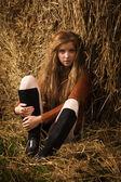 Pretty girl resting on straw bale — Stock Photo