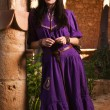 Brunette girl in a medieval suit in a Agia Napa Medieval Monaste - Stock Photo