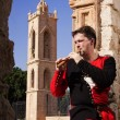 Man in a medieval suit plays a flute — Stock Photo #16916875