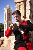Hombre con un traje medieval toca una flauta — Foto de Stock
