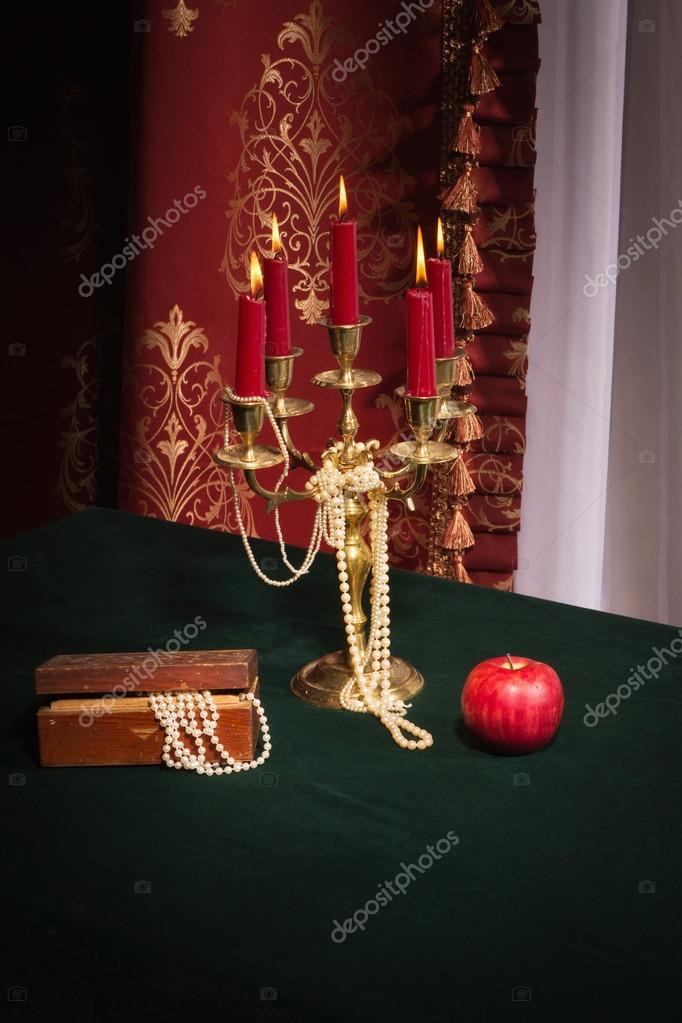 Composition with apple, candlestick and jewellery box on red background — Stock Photo #16955219