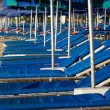 Roe of striped deck chairs on the beach - Stock Photo