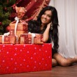 Happy brunette sitting near a Christmas tree with gifts — Foto de Stock