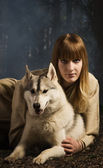 Slavonian girl and siberian husky in the deep forest — Stock Photo