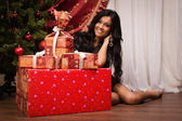 Happy brunette sitting near a Christmas tree with gifts — Stock Photo