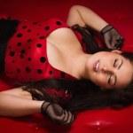 garota Pin-up, deitada em um sofá de couro vermelho — Foto Stock
