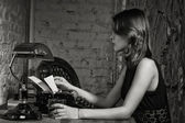 Elegant woman in black with the old typewriter — Stock Photo