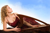 Blonde woman with a harp in his hand — Stock Photo