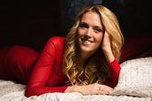 Sensuell blond i en röd klänning som ligger på sängen — Stockfoto