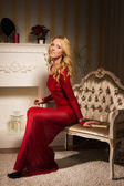 Romantic portrait of a beautiful blonde lady in a red dress — Stock Photo
