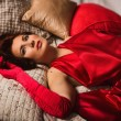 Sensual brunette in a red dress lying on the bed — Stock Photo