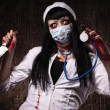 Crazy dead nurse with knife in the hand - Stock Photo