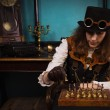Steam punk girl plays chess — Stock Photo