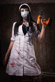 Crazy dead nurse with drill in the hand — Stock Photo