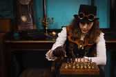 Steam punk girl plays chess — Stock Photo