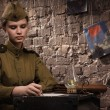 Soviet female soldier in uniform of World War II writes a letter - Стоковая фотография