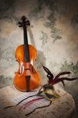 Violino com pontuação e máscara em uma parede de pedra — Fotografia Stock