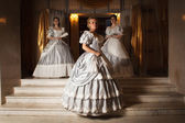 Three young women in ball gowns — Stock Photo