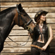 Cowgirl and brown horse — Stock Photo #27766545