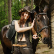 Cowgirl with brown horse — Stock Photo #27766663