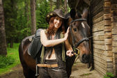 Cowgirl with brown horse — Stock Photo