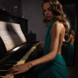 Beauty woman in evening dress playing piano — Stock Photo